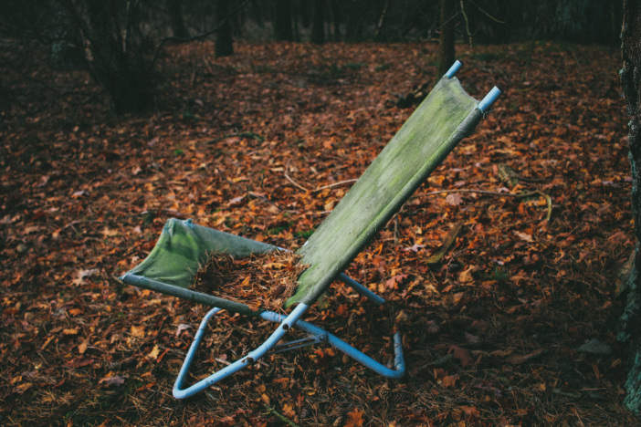 An old lawn chair in the woods, decrepit and covered in leaves