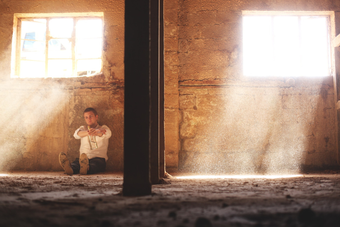A man sitting on the ground in an empty room, dust visible from the light streaming through the windows